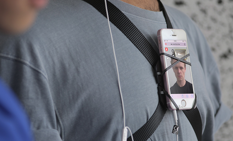 Proxy protester with phone strapped to his chest. The phone has an image of a face on itr